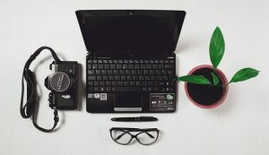 Laptop with camera, glasses and plant